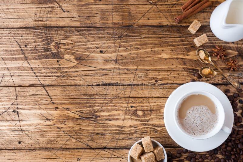 Taza de café, de azúcar marrón y de canela con anís en un fondo de madera Copie el espacio fotos de archivo