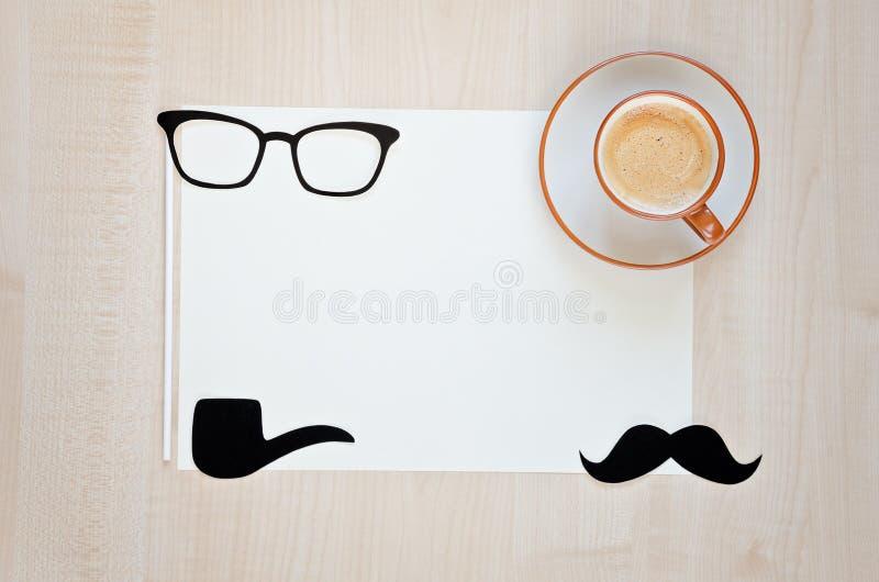 Taza de café, bigote, vidrios, tubo que fuma y taza de café en fondo de madera Fondo feliz del día del ` s del padre fotografía de archivo