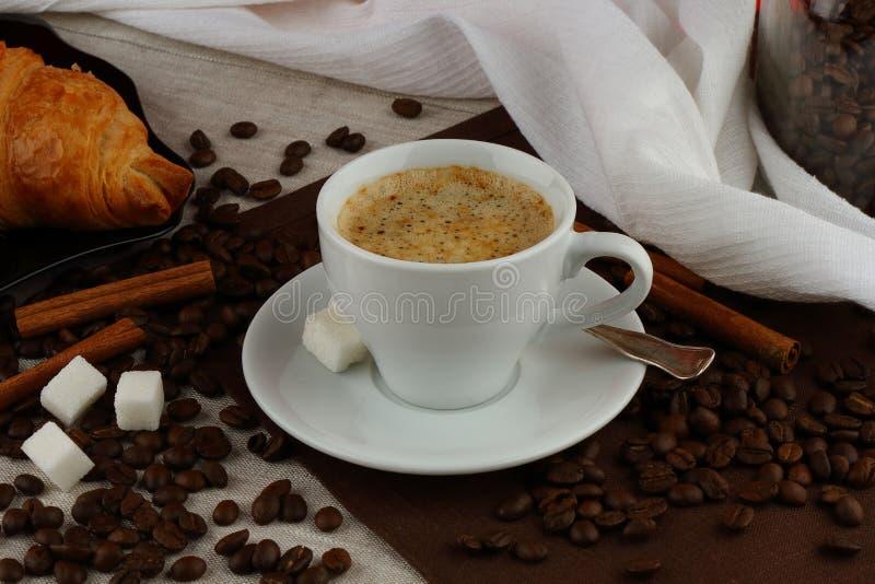 Taza de café blanca con el cruasán en las servilletas de lino imagen de archivo libre de regalías