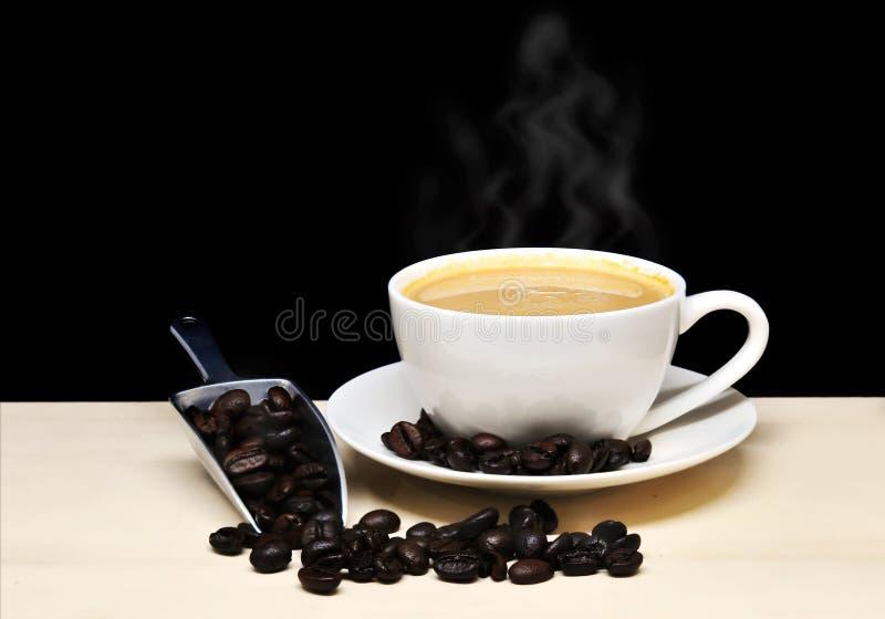 Taza de café caliente con los granos del humo y de café con la cucharada, comida y imagenes de archivo