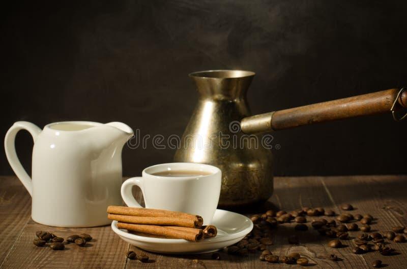 Taza de café caliente con los palillos de canela con una desnatadora y un pote viejo/una taza de café caliente con los palillos d imagen de archivo libre de regalías
