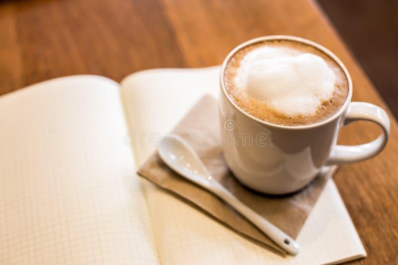 Taza de café caliente del arte del latte en la tabla y el cuaderno de madera, vintage fotos de archivo