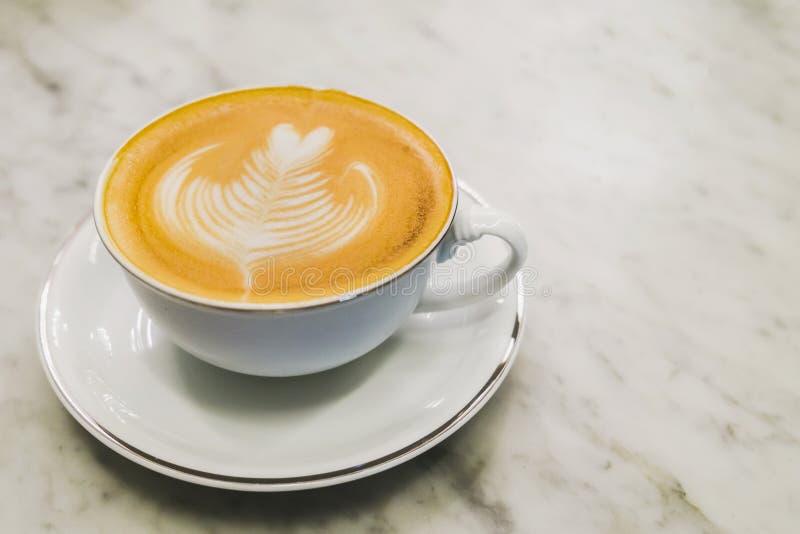 Taza de café caliente del arte del latte en la tabla de mármol foto de archivo libre de regalías