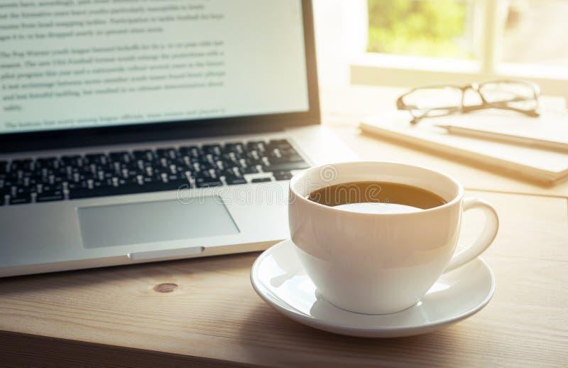 Taza de café caliente en el escritorio de madera con el ordenador portátil y el cuaderno imagen de archivo libre de regalías