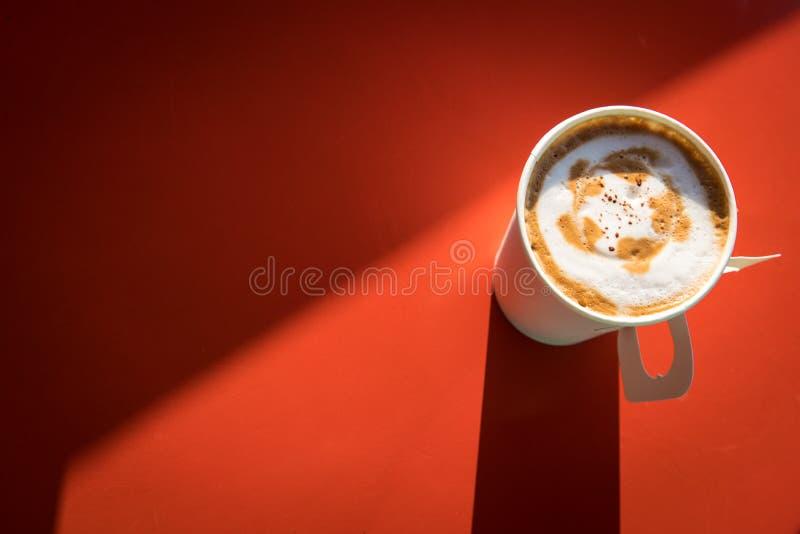 Taza de café caliente para llevar en la tabla roja con el espacio de la copia imagen de archivo