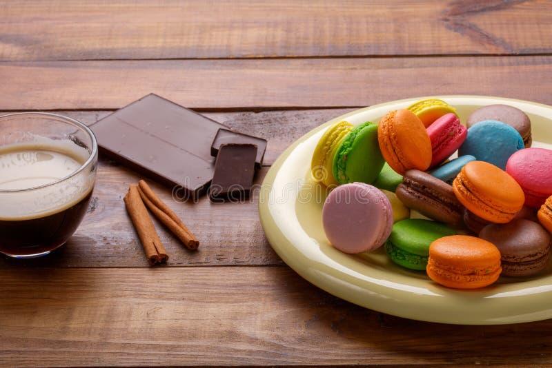 Taza de café, canela, chocolate y macarrones en la tabla de cocina vieja foto de archivo