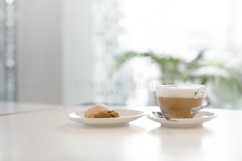 Taza de café cerca de la placa con la galleta foto de archivo libre de regalías