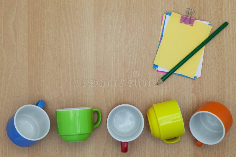 Taza de café colorida con la nota de papel, lápiz en el fondo de madera fotografía de archivo libre de regalías