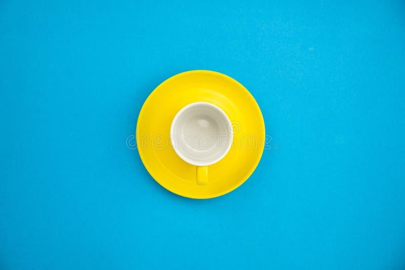 Taza de café colorida en fondo de papel azul foto de archivo
