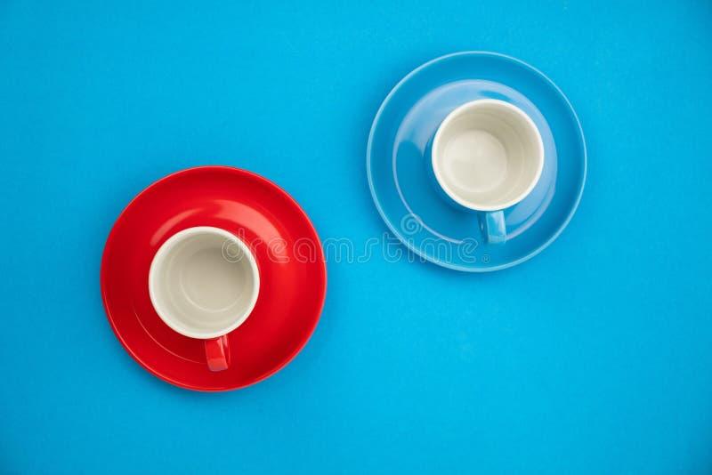 Taza de café colorida en fondo de papel azul imagenes de archivo