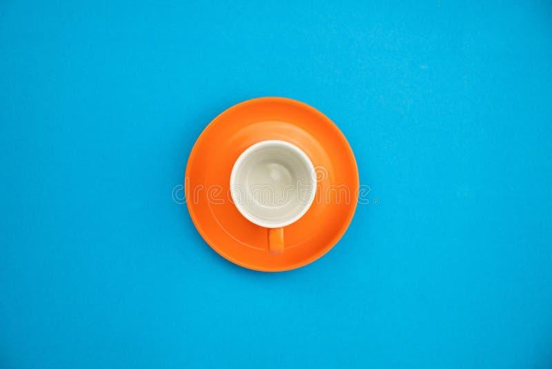 Taza de café colorida en fondo de papel azul fotos de archivo