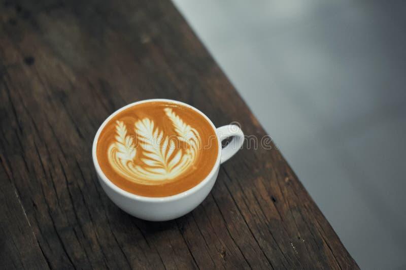 Taza de café con arte del latte en la tabla de madera imagen de archivo libre de regalías