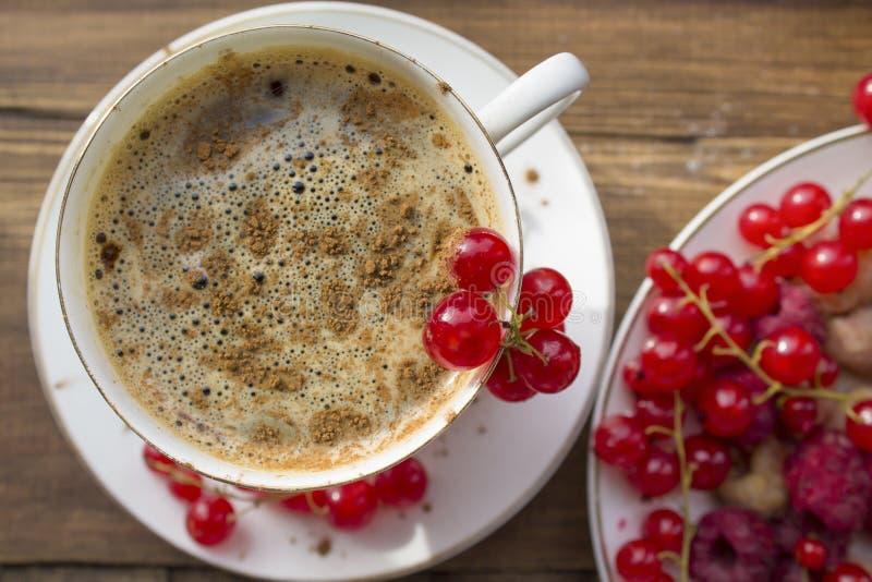 Taza de café con canela y bayas frescas foto de archivo