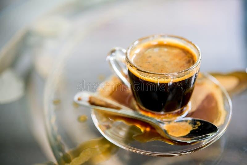 Taza de café con café derramado en la tabla imagen de archivo libre de regalías