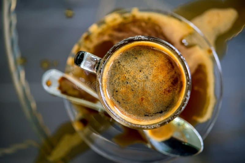 Taza de café con café derramado en la tabla foto de archivo