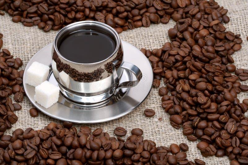 Taza de café con el azúcar y las habas de terrón imagen de archivo