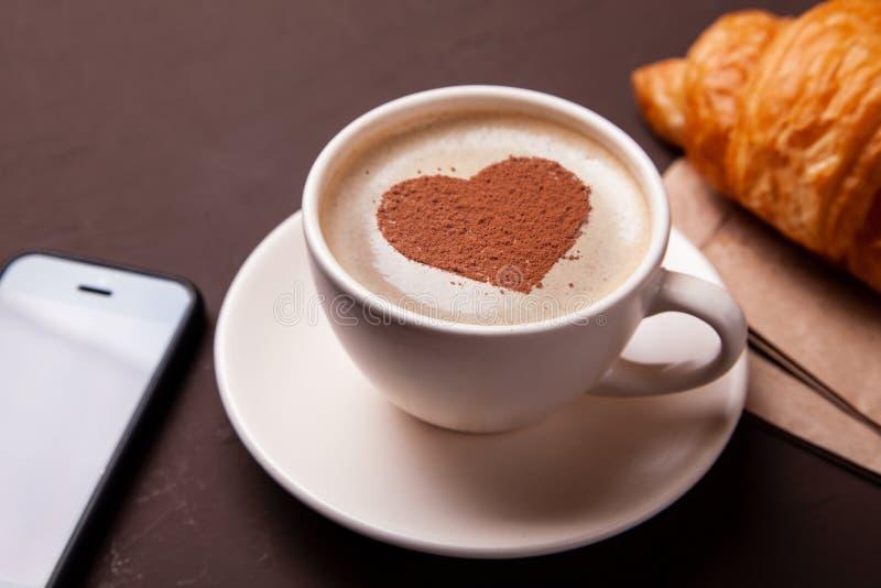 Taza de café con el corazón en la espuma Tengo gusto al descanso para tomar café con el cruasán foto de archivo libre de regalías