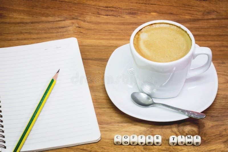 Taza de café con el cuaderno y el lápiz foto de archivo