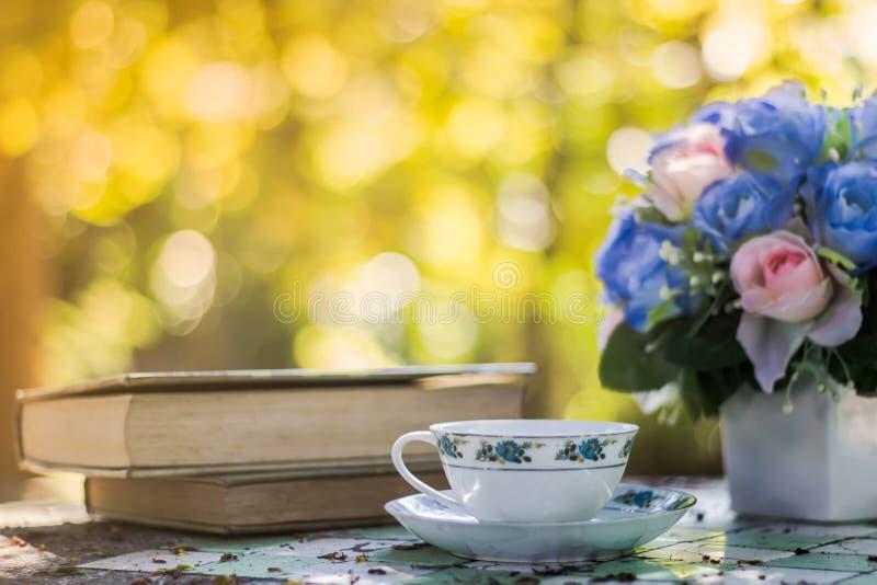 Taza de café con el escritorio de la flor, libro suave de la falta de definición del fondo del foco imagen de archivo