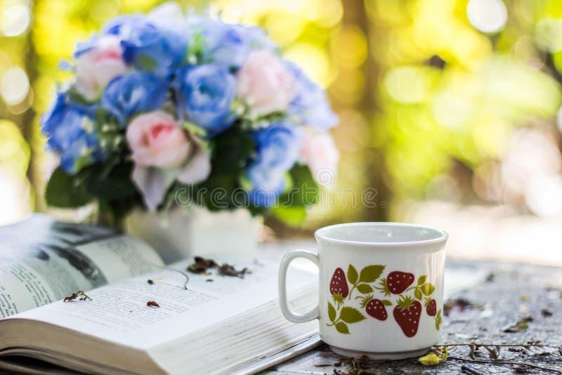 Taza de café con el escritorio de la flor, libro suave de la falta de definición del fondo del foco fotografía de archivo libre de regalías