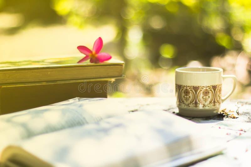 Taza de café con el escritorio de la flor, libro suave de la falta de definición del fondo del foco foto de archivo