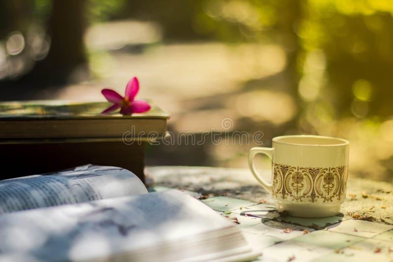 Taza de café con el escritorio de la flor, libro suave de la falta de definición del fondo del foco fotos de archivo