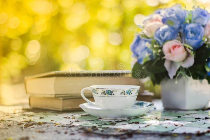 Taza de café con el escritorio de la flor, libro suave de la falta de definición del fondo del foco foto de archivo libre de regalías