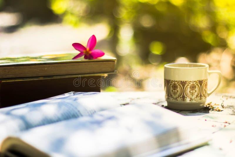 Taza de café con el escritorio de la flor, libro suave de la falta de definición del fondo del foco imágenes de archivo libres de regalías