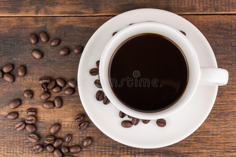 Taza de café con el grano de café imagenes de archivo