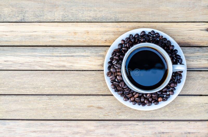 Taza de café con el grano de café en la opinión de madera de la tabla del top fotos de archivo