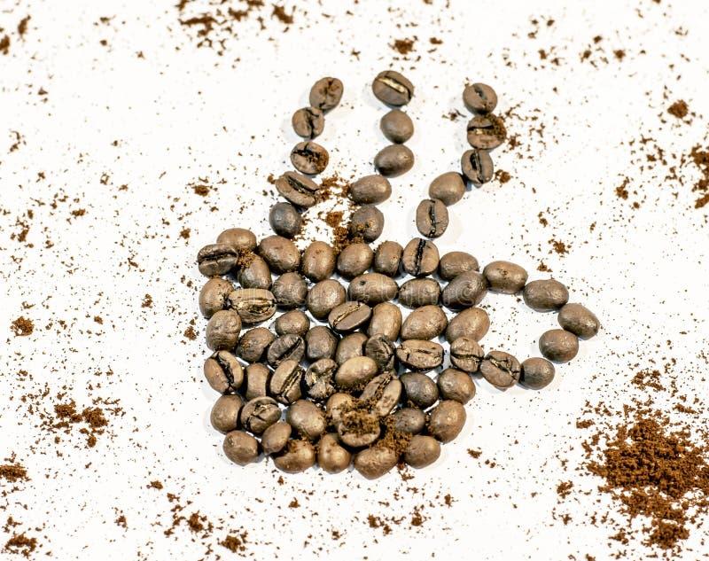 Taza de café con el humo hecho del grano de café asperjado con café fresco foto de archivo