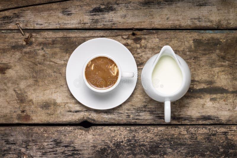 Taza de café con el jarro de leche en los antecedentes de madera Visión superior imagen de archivo libre de regalías
