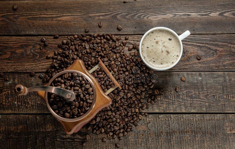 Taza de café con el molino y habas en la tabla oscura Visión superior imagen de archivo libre de regalías