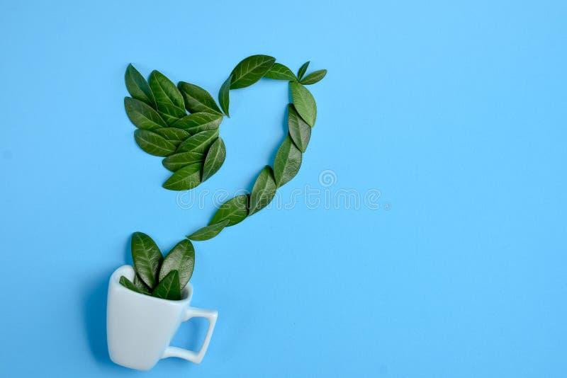 Taza de caf? con el p?jaro hecho de hojas verdes naturales en fondo azul Endecha plana, visi?n superior, espacio de la copia libre illustration