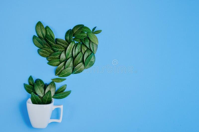 Taza de caf? con el p?jaro hecho de hojas verdes naturales en fondo azul Endecha plana, visi?n superior, espacio de la copia stock de ilustración