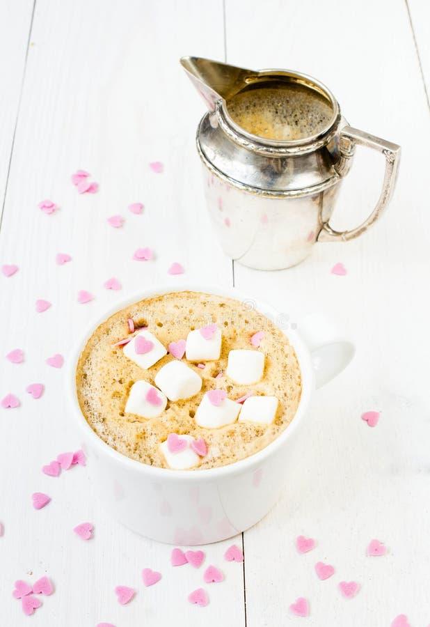 Taza de café con espuma, la melcocha, la taza de la leche y el dulce comestible foto de archivo