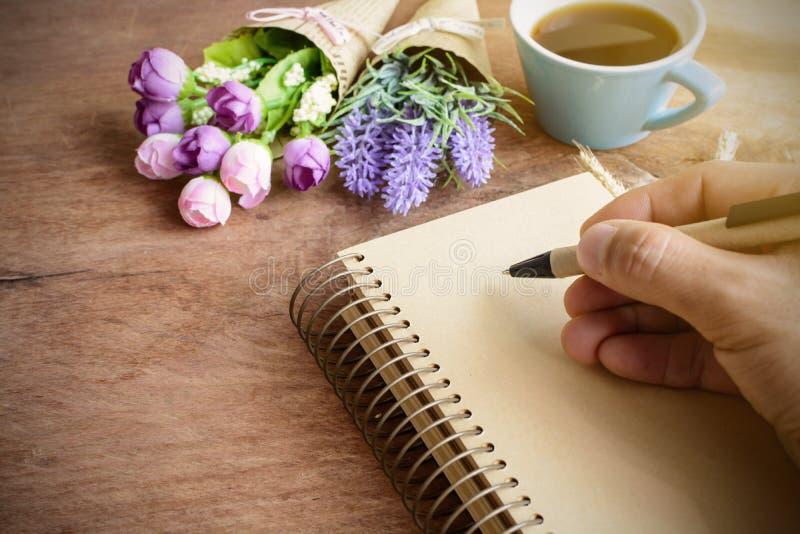 Taza de café con la flor y el cuaderno en blanco en la tabla de madera fotos de archivo libres de regalías