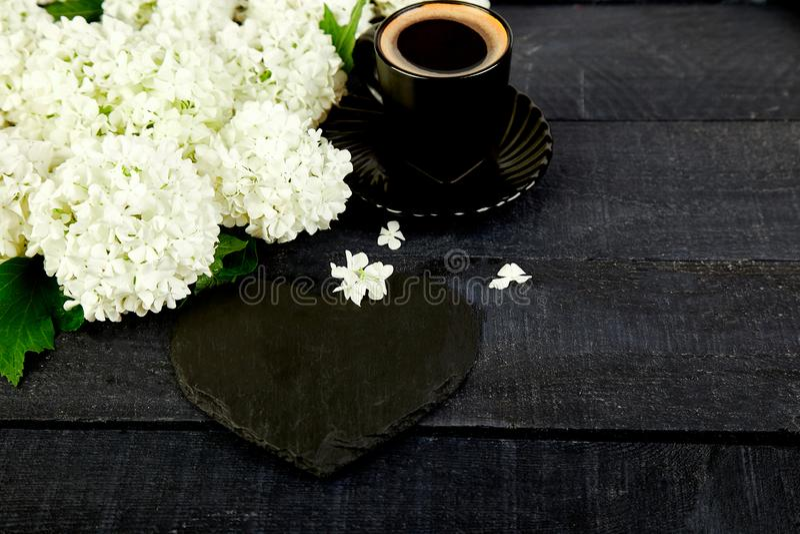 Taza de café con la hortensia de la flor del ramo y el corazón de la pizarra imagenes de archivo