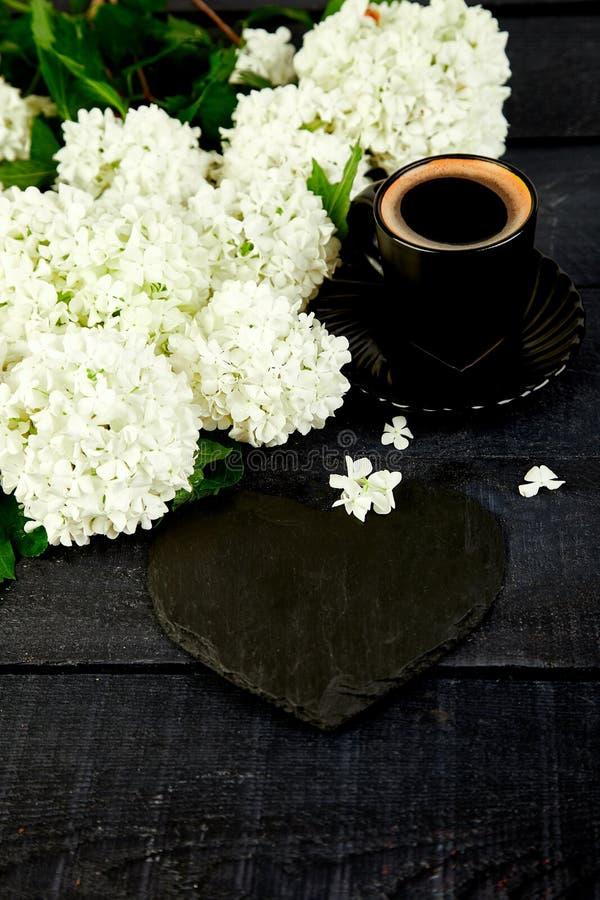 Taza de café con la hortensia de la flor del ramo y el corazón de la pizarra fotos de archivo libres de regalías