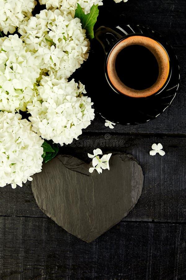 Taza de café con la hortensia de la flor del ramo y el corazón de la pizarra foto de archivo