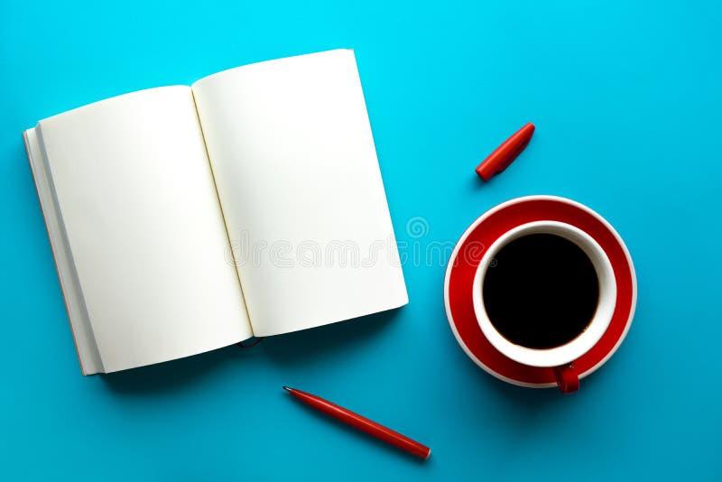 Taza de café con la libreta en blanco en la tabla de color en colores pastel ideas de la creatividad foto de archivo libre de regalías