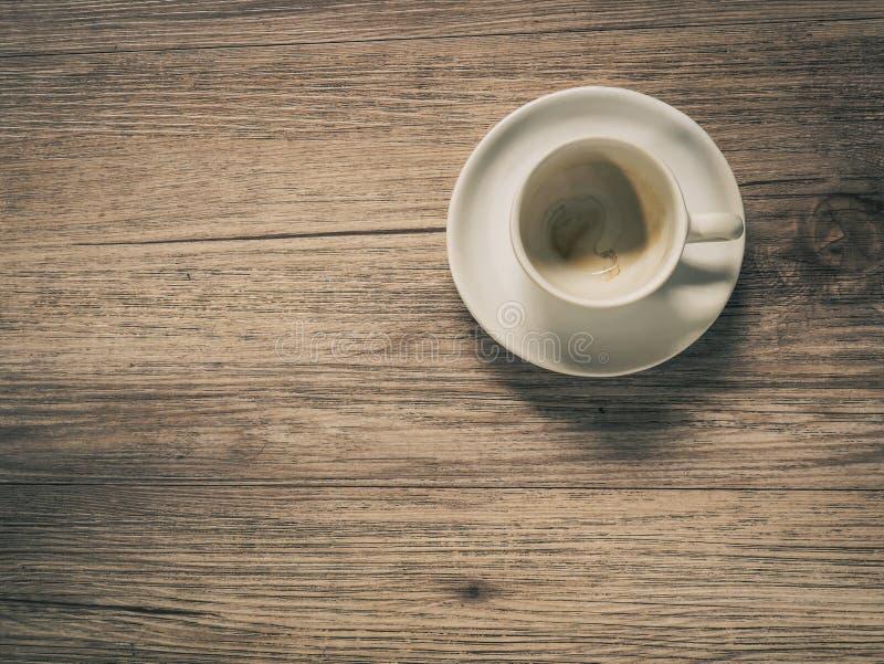 Taza de café con la mancha en la tabla de madera imagen de archivo