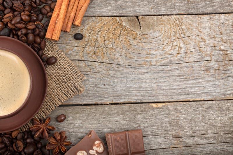 Taza de café con las especias y el chocolate en textura de madera de la tabla fotos de archivo libres de regalías