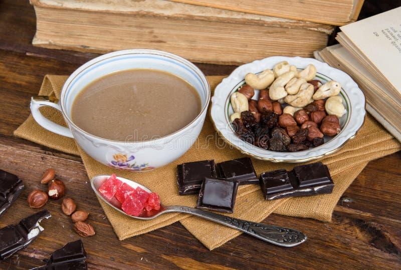 Taza de café con las frutas y el chocolate secos en servilleta foto de archivo libre de regalías