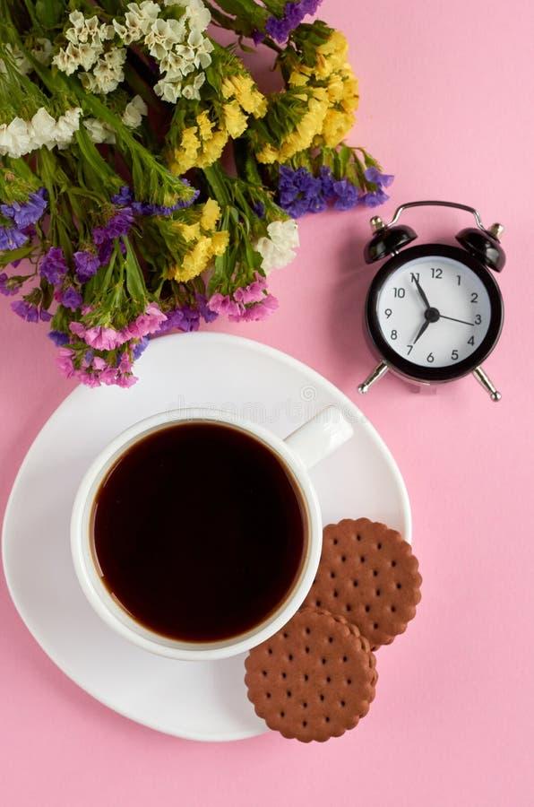 Taza de café con las galletas, despertador, flores, en la composición rosada del fondo foto de archivo libre de regalías