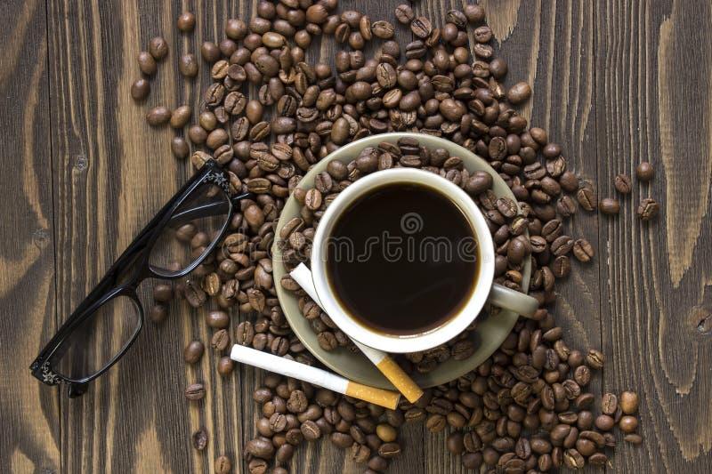 Taza de café con las habas, dos cigarrillos y vidrios imagen de archivo libre de regalías