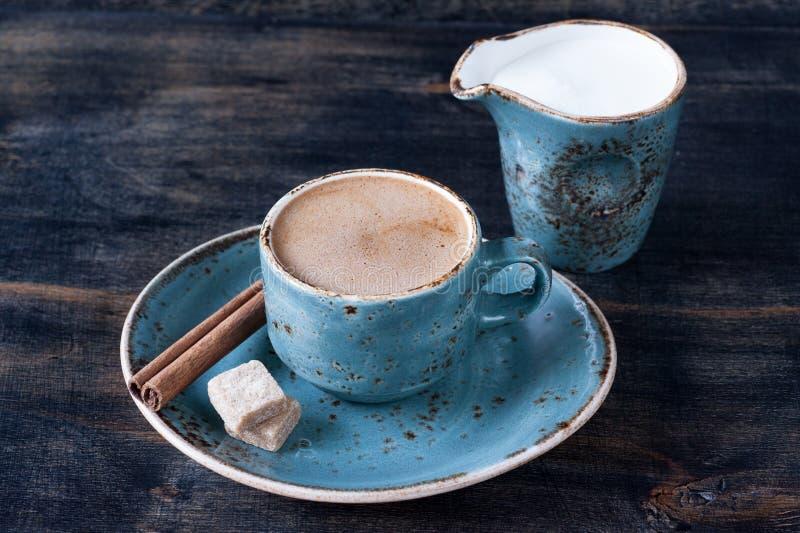 Taza de café con leche, canela y azúcar foto de archivo