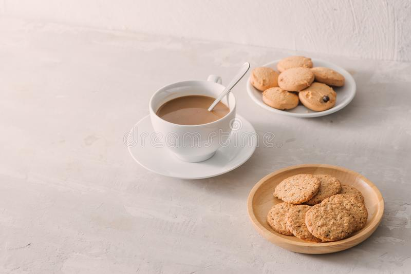 Taza de café con leche o capuchino con las galletas en fondo de piedra ligero Bebida con cafeína o cacao con leche Descanso para  imagenes de archivo