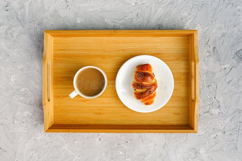 Taza de café con leche y el cruasán recientemente cocido en la bandeja de madera en la tabla de piedra gris Opinión de top de la  foto de archivo