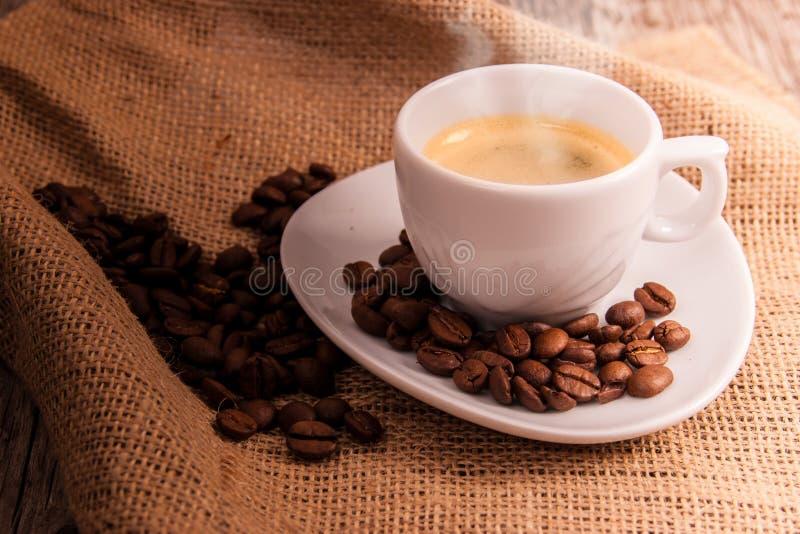 Taza de café con los granos de café fotografía de archivo